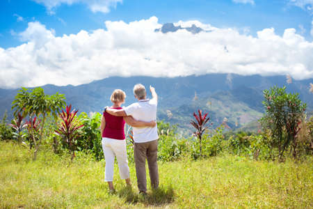 Senior couple hiking in mountains. Mature man and woman trekking in Borneo jungle. Family looking at Mount Kinabalu peak, highest mountain of Malaysia. Summer vacation in Southeast Asia. 写真素材