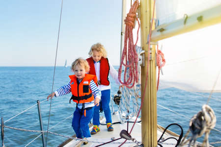 Kids sail on yacht in sea. Child sailing on boat. Little boy and girl in safe life jackets travel on ocean ship. Children enjoy yachting cruise. Summer vacation for family. Young sailors on sailboat.