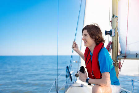 Jugendlicher Junge, der lernt, auf Yacht im Meer zu segeln. Junger Mann, der auf Boot segelt. Seemann in sicherer Schwimmweste. Teenager auf Yachtkreuzfahrt. Sommerurlaub. Kind auf Segelboot. Standard-Bild