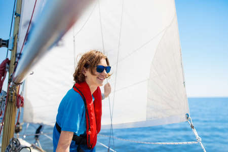 Teen age boy learning to sail on yacht in the sea. Young man sailing on boat. Sailor in safe life jacket. Teenager on yachting cruise. Summer vacation. Kid on sailboat.