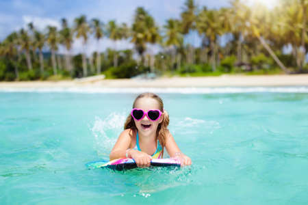 Child surfing on tropical beach. Family summer vacation in Asia. Kids swim in ocean water. Kid on surf body board. Little girl swimming in exotic sea. Travel with children. Water and beach sport.