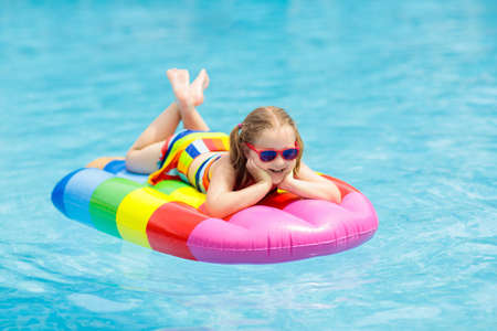 Happy child on inflatable ice cream float in outdoor swimming pool of tropical resort. Summer vacation with kids. Swim aids and wear for children. Water toys. Little girl floating on colorful raft. Reklamní fotografie - 101296317