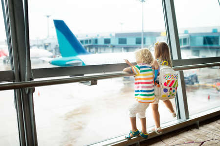 Kids at airport. Children look at airplane. Traveling and flying with child. Family at departure gate. Vacation and travel with young kid. Boy and baby before flight in terminal. Kids fly a plane. Archivio Fotografico - 101489183