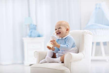 Entzückender kleiner Junge, der auf einer blauen Bodenmatte spielt und Milch von einer Flasche in einem weißen sonnigen Kinderzimmer mit Schaukelstuhl und Stubenwagen trinkt. Schlafzimmer Interieur mit Babybett. Formelgetränk für Kleinkinder.