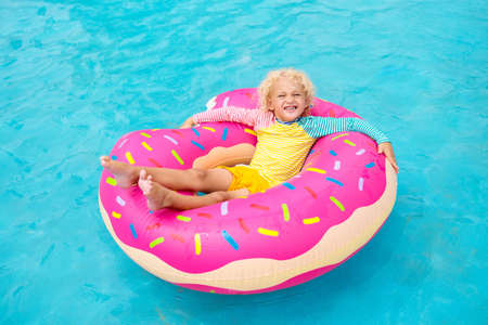 Child in a swimming pool on a funny inflatable donut float ring. Little boy learning to swim in an outdoor pool of tropical resort. Water toys for kids. Healthy sport activity for children. Sun protection.