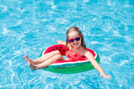 Child with watermelon. Little girl learning to swim in outdoor pool of tropical resort. Kid eye wear. Water toys and floats for kids. Healthy sport for children.