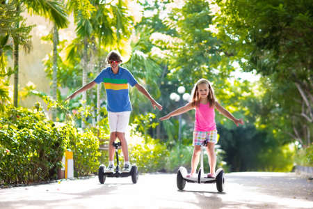 Child on hover board. Kids riding scooter in summer park. Balance board for children. Electric self balancing scooter. Girl and boy learning to ride hoverboard. Modern gadgets for school kid. Stock Photo