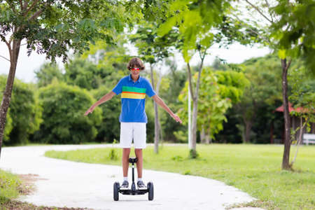 Child on hover board. Kids riding scooter in summer park. Balance board for children. Electric self balancing scooter on city street. Boy learning to ride hoverboard. Modern gadgets for school kid. Stock Photo - 101490437