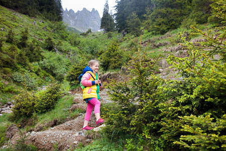 Children hiking in Alps mountains. Kids look at snow covered mountain in Austria. Spring family vacation. Little girl on hike trail in blooming alpine meadow. Outdoor fun and healthy activity. Standard-Bild - 102703181