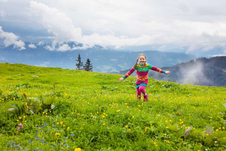 Little girl on hike trail in blooming alpine meadow. Outdoor fun and healthy activity.