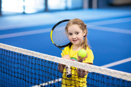 Child playing tennis on indoor court. Little girl with tennis racket and ball in sport club. Active exercise for kids. Summer activities for children. Training for young kid. Child learning to play. Archivio Fotografico - 102724540