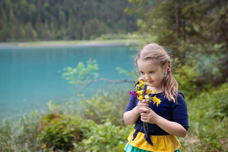 Child hiking in the Alps mountains looking at beautiful lake.