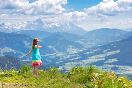 Children hiking in Alps mountains. Kids look at snow covered mountain in Austria. Spring family vacation. Little girl on hike trail in blooming alpine meadow. Outdoor fun and healthy activity.