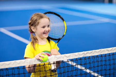 Child playing tennis on indoor court. Little girl with tennis racket and ball in sport club. Active exercise for kids. Summer activities for children. Training for young kid. Child learning to play. Archivio Fotografico - 102703183