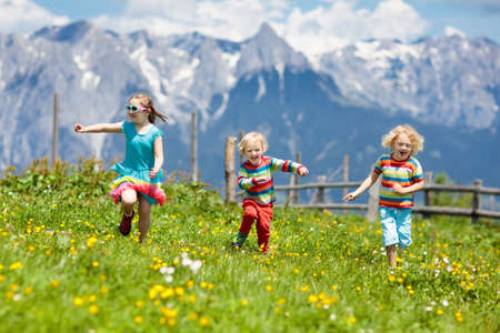 Children hiking in Alps mountains. Kids run at snow covered mountain in Austria. Spring family vacation. Little boy and girl on hike trail in blooming alpine meadow. Outdoor fun and healthy activity. 免版税图像