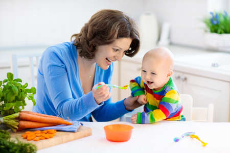 Mother feeding child. First solid food for young kid. Fresh organic carrot for vegetable lunch. Stock Photo