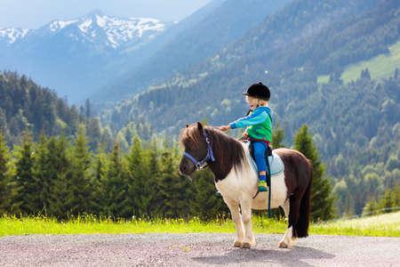Kid rijden pony in de bergen van de Alpen. Familie voorjaarsvakantie op paardenranch in Oostenrijk, Tirol.