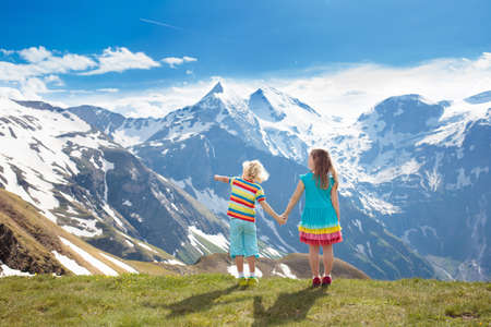 Little boy and girl on hike trail in blooming alpine meadow. Outdoor fun and healthy activity. Standard-Bild - 102744132