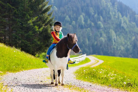 Kid riding pony in the Alps mountains. Family spring vacation on horse ranch in Austria, Tirol.