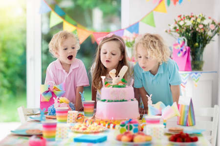 Kids birthday party. Children blow out candles on pink bunny cake. Pastel rainbow decoration and table setting for kids event, banner and flag.