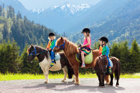 Kids riding pony in the Alps mountains. Family spring vacation on horse ranch in Austria, Tirol.