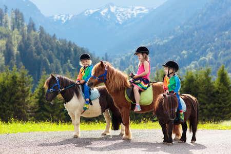 Kinder reiten Pony in den Alpen. Familienfrühlingsurlaub auf Pferderanch in Österreich, Tirol.
