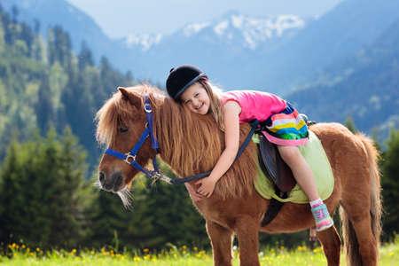 Kinderen rijden pony in de bergen van de Alpen. Familie voorjaarsvakantie op paardenranch in Oostenrijk, Tirol. Stockfoto