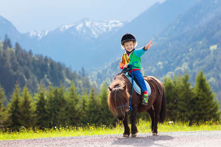 Kid riding pony in the Alps mountains.