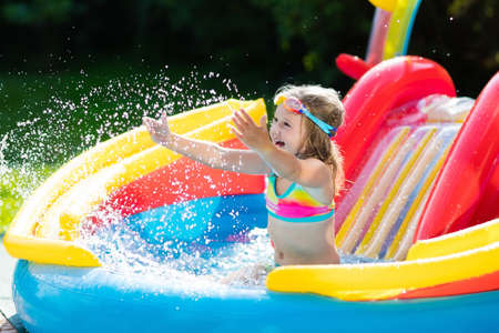 Child playing in inflatable baby pool. Kids swim, slide and splash in colorful garden play center.