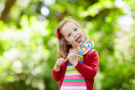 Cute little girl with big colorful lollipop. Child eating sweet candy bar.
