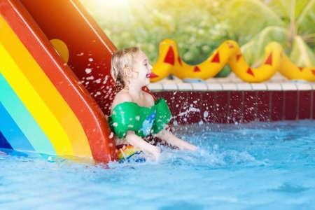 Child on swimming pool slide. Kid having fun sliding in water amusement park. Stock Photo
