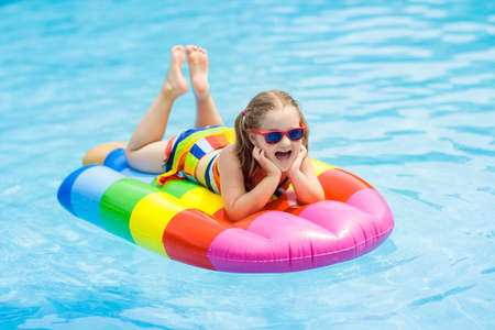 Happy child on inflatable ice cream float in outdoor swimming pool of tropical resort.