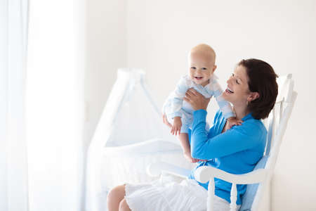 Young mother holding her newborn child. Mom nursing baby. Stock Photo