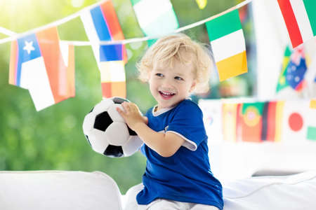 Child watching football game on tv. Little boy in France tricot watching soccer game during championship. Banco de Imagens