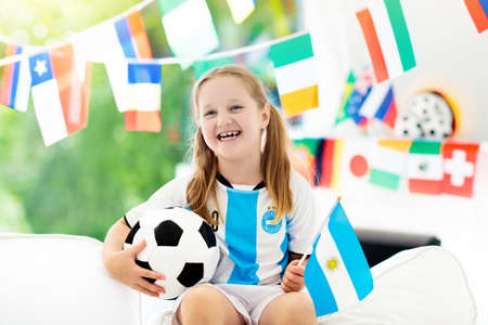 Child watching football game on tv. Girl in Argentina jersey watching soccer game during championship. Banco de Imagens