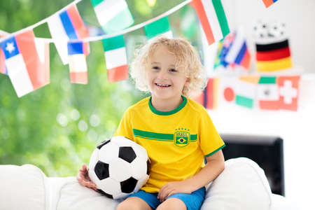 Child watching football game on tv. Little boy in Brazil tricot watching soccer game during championship. Banco de Imagens