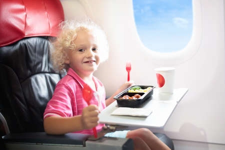 Child in airplane window seat. Kids flight meal. Children fly. Special inflight menu, food and drink for baby and kid. Little boy eating healthy lunch in airplane. Travel with kids. Family vacation. Imagens