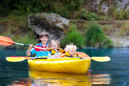 Child with paddle on kayak. Summer camp for kids. Kayaking and canoeing with family. Children on canoe. Little boy on kayak ride. Wild nature and water fun on summer vacation. Camping and fishing. Stockfoto - 102944603