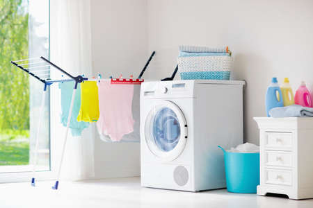 Laundry room with washing machine or tumble dryer. Modern household devices in white sunny home. Clean washed clothes on drying rack. Liquid washing detergent in plastic bottle and fabric softener.