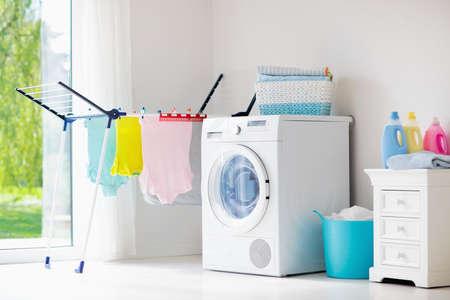 Waschküche mit Waschmaschine oder Wäschetrockner. Moderne Haushaltsgeräte im weißen sonnigen Haus. Waschen Sie gewaschene Kleidung auf dem Wäscheständer. Flüssiges Waschmittel in Plastikflasche und Weichspüler.