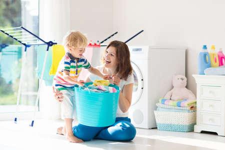 Matka i dzieci w pralni z pralką lub suszarką. Obowiązki rodzinne. Nowoczesne urządzenia gospodarstwa domowego i detergent do prania w białym słonecznym domu. Wyprane ubrania wyczyść na suszarce.