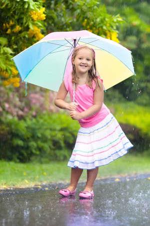 Bambino che gioca sotto la pioggia. I bambini con l'ombrello giocano all'aperto sotto la pioggia. Bambina sorpresa nella prima doccia di primavera. Divertimento all'aria aperta per bambini dal tempo piovoso autunnale. Bambino che corre nella tempesta tropicale.