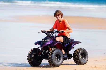 Teenager riding quad bike on tropical beach. Active teen age boy on quadricycle. All-terrain vehicle ride. Motor cross sports on ocean sand dune. Off road race at sea shore. Summer vacation activity. Stockfoto