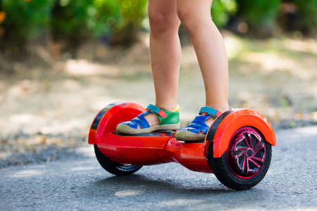 Child on hover board. Kids riding scooter in summer park. Balance board for children. Electric self balancing scooter on city street. Girl learning to ride hoverboard. Modern gadgets for school kid. Stock Photo - 102945280