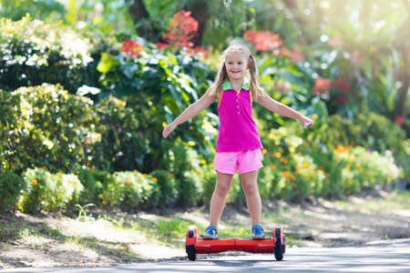 Child on hover board. Kids riding scooter in summer park. Balance board for children. Electric self balancing scooter on city street. Girl learning to ride hoverboard. Modern gadgets for school kid. Stock Photo - 102945714
