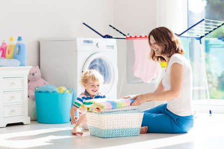 Mother and kids in the laundry room with washing machine or tumble dryer. Family chores. Modern household devices and washing detergent in white sunny home. Clean washed clothes on drying rack.