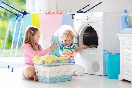 Kinder in der Waschküche mit Waschmaschine oder Wäschetrockner. Kinder helfen bei der Hausarbeit. Moderne Haushaltsgeräte und Waschmittel im weißen sonnigen Haus. Waschen Sie gewaschene Kleidung auf dem Wäscheständer.
