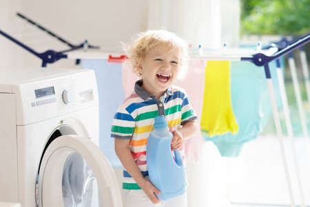 Child in a laundry room with washing machine or tumble dryer. Kid helping with family chores. Modern household devices and washing detergent in white sunny home. Clean washed clothes on drying rack. Stockfoto