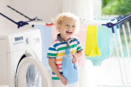 Niño en un lavadero con lavadora o secadora. Niño ayudando con las tareas familiares. Aparatos domésticos modernos y detergente en casa soleada blanca. Limpiar la ropa lavada en la rejilla de secado.