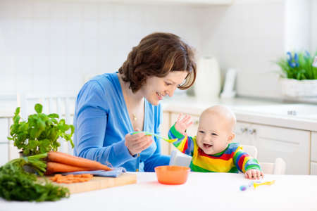 Mother feeding child. First solid food for young kid. Fresh organic carrot for vegetable lunch. Baby weaning. Mom and little boy eat vegetables. Healthy nutrition for children. Parents feed kids.